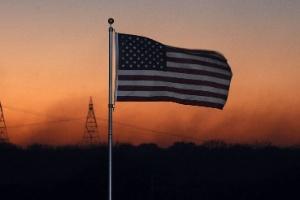 Bandeira norte-americana é vista em frente a incêndio na região de Oak Hills, na Califórnia (EUA)