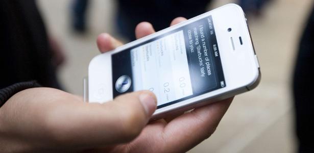 Usuário segura iPhone 4S, smartphone da Apple, à venda em loja de Nova York (EUA) durante estreia