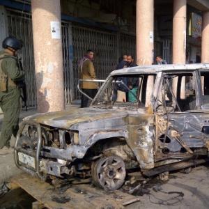Militares observam carro queimado em ataque com bombas realizado na região central de Bagdá
