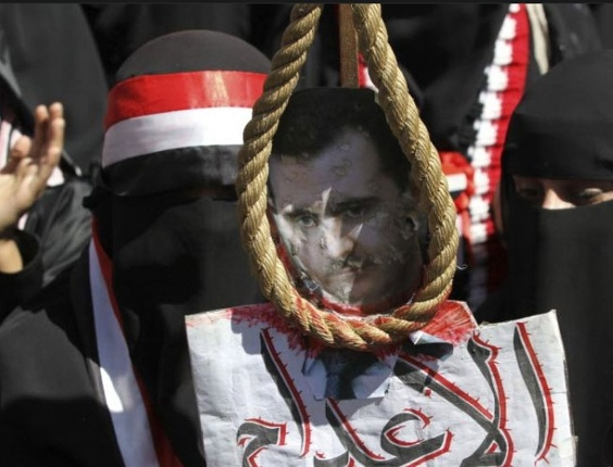 """Mulheres seguram uma foto do presidente da Síria, Bashar al-Assad, mostrado com uma corda de forca ao redor do pescoço, durante uma passeata realizada em Sanaa, Iêmen, em solidariedade aos rebeldes sírios anti-governo. Na placa lê-se """"morte"""""""