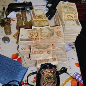 Notas e armas apreendidas pela Polícia Federal na casa de Antonio Jussivan Alves dos Santos, o Alemão, em Brasília, DF. Ele é o principal suspeito de ter articulado o furto de R$ 164 milhões do BC em 2005