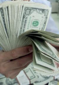Homem conta cédulas de dólar