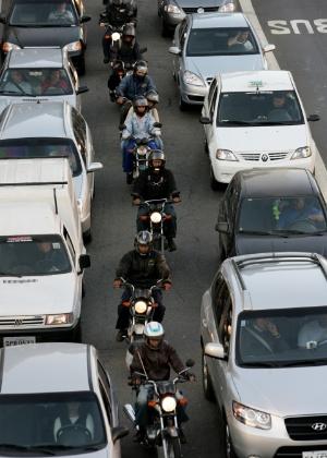 Motos avançam pelo corredor em via paulistana