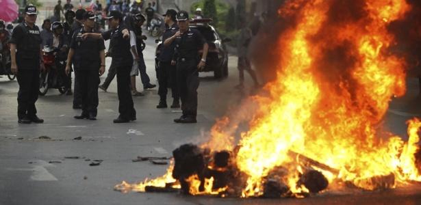 """Oficiais da Tailândia ao lado de fogueira improvisada pelos """"camisas vermelhas"""" em Bancoc"""