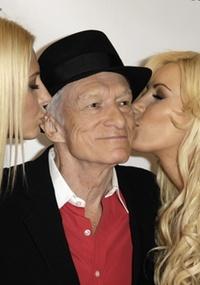 Hugh Hefner, fundador da 'Playboy' é beijado por duas modelos da revista
