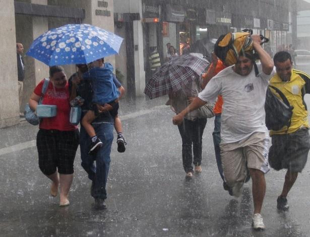 Paulistanos correm da chuva; apesar de o Sol estar escondido neste verão, chove dentro da média
