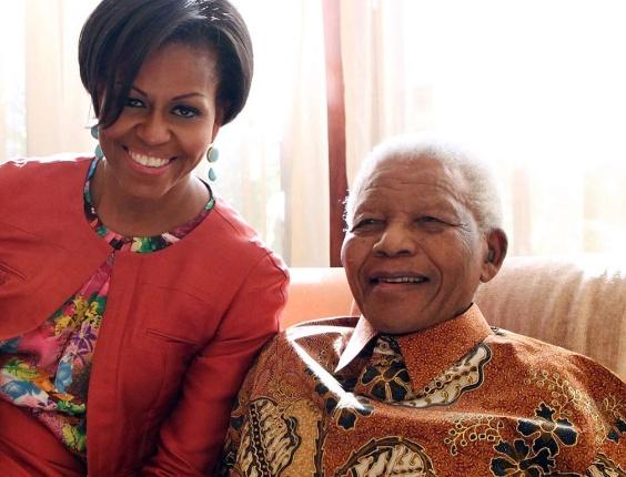Michelle Obama junto ao ex-presidente sul-africano Nelson Mandela na primeira visita internacional da primeira-dama dos EUA sem o marido