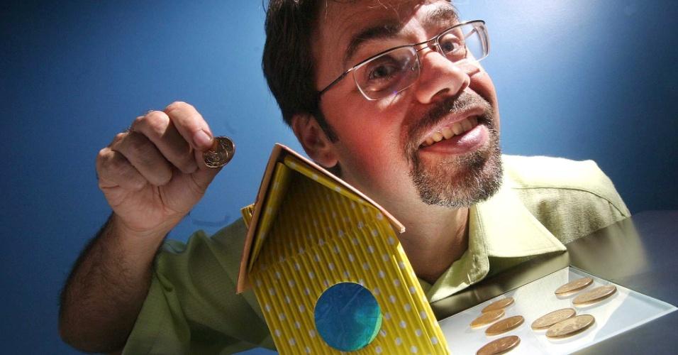 Jose Ivo, que fez empréstimo na Caixa Econômica Federal para a reforma de seu imóvel, coloca moeda em maquete de casa para simbolizar o financiamento imobiliário