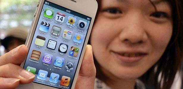 Cliente segura aparelho após lançamento no Japão; Brasil tem iPhone 4S mais caro do mundo