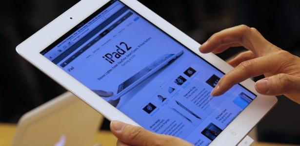 Usuário avalia tablet iPad 2 exposto em loja da Apple em Hong Kong