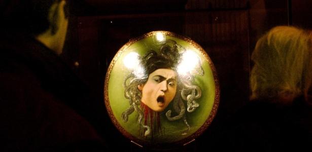 Em Milão, visitantes olham para o escudo cerimonial com retrato da Medusa, pintado por volta de 1600 por Michelangelo Merisi, conhecido por Caravaggio (27/5/93) - Luca Bruno/AP
